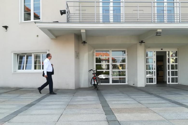 Mężczyzna w białej koszuli z marynarką na ramieniu wchodzi do budynku