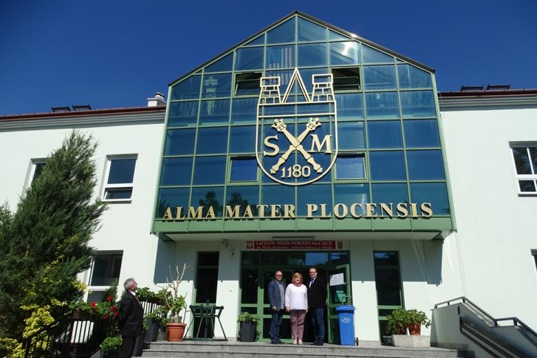 Trzy odoby na stopniach budynku z napisem Alma Mater Plocensis