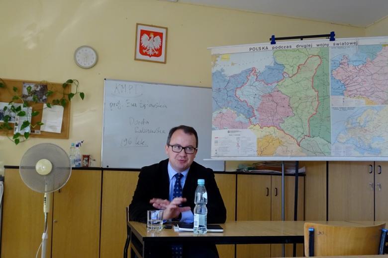 Męzczyzna za stołem nauczycielskim, na tablicy napisy: KMPT, prof. Ewa Łętowska, Doda Rabczewska, 96 kk