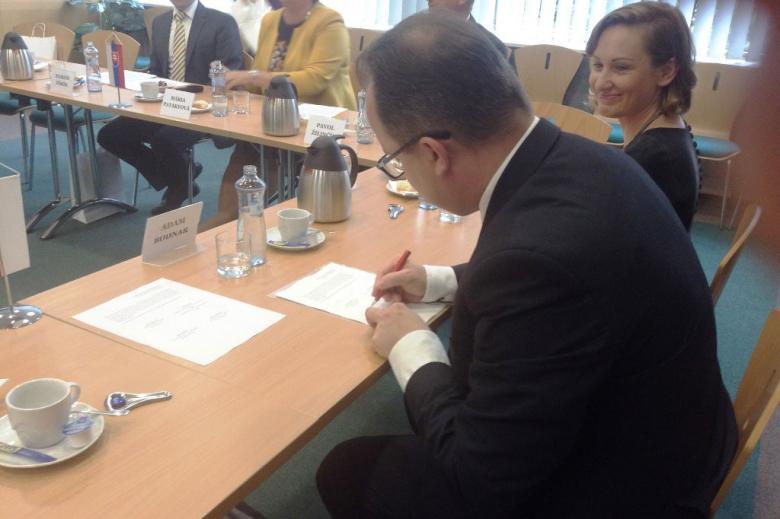 zdjęcie: mężczyzna siedzi przy stole i podpisuje dokument