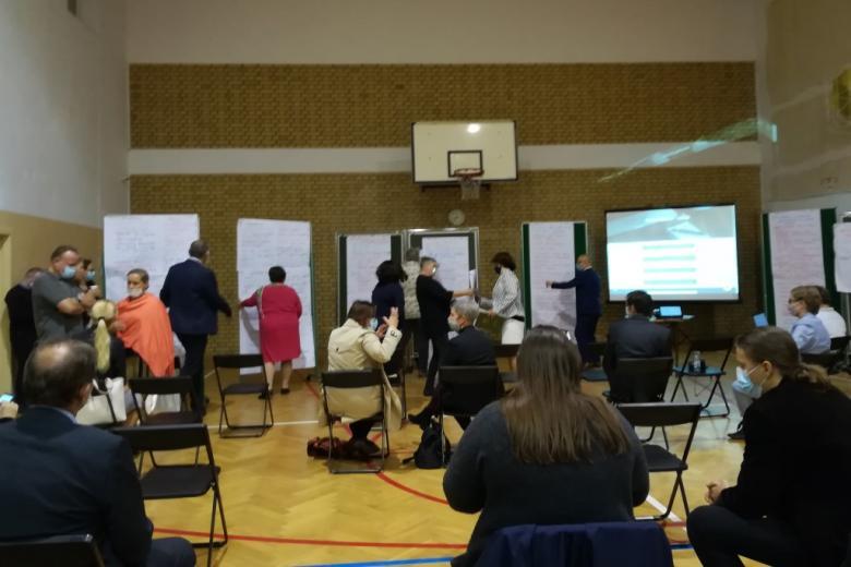 Ludzie gromadzą się na sali wokół zapisanych tablic