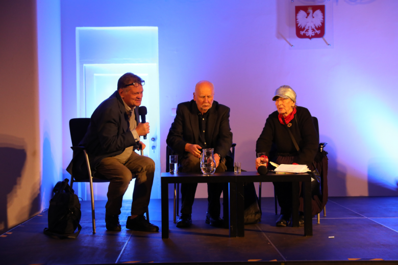 Trzy osoby rozmawiają na scenie