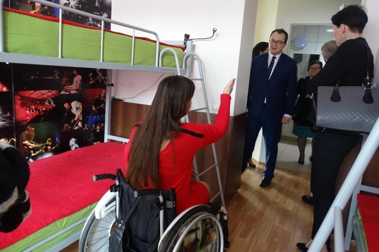 Młoda kobieta w czerwonej sukni i na wózku rozmawia z mężczyzną w garniturze