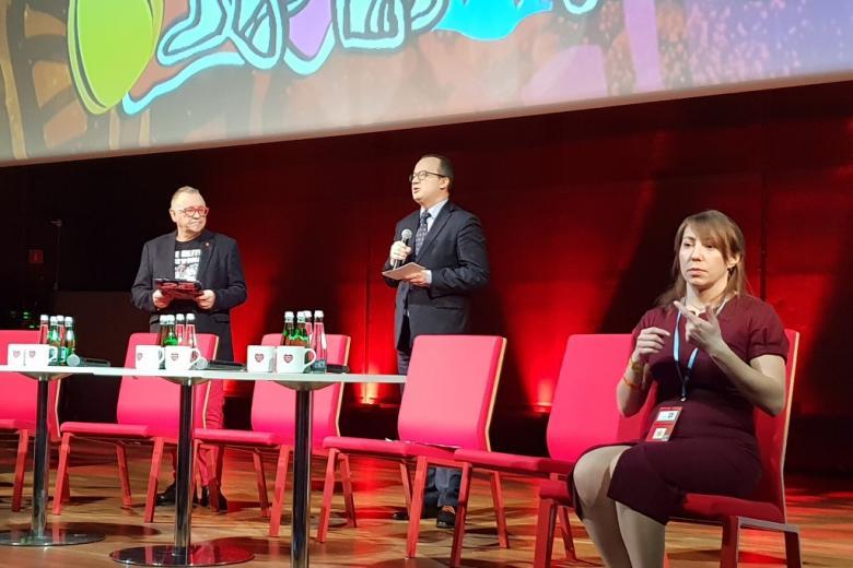 dwaj mężczyźni na scenie oraz tłumaczka języka migowego