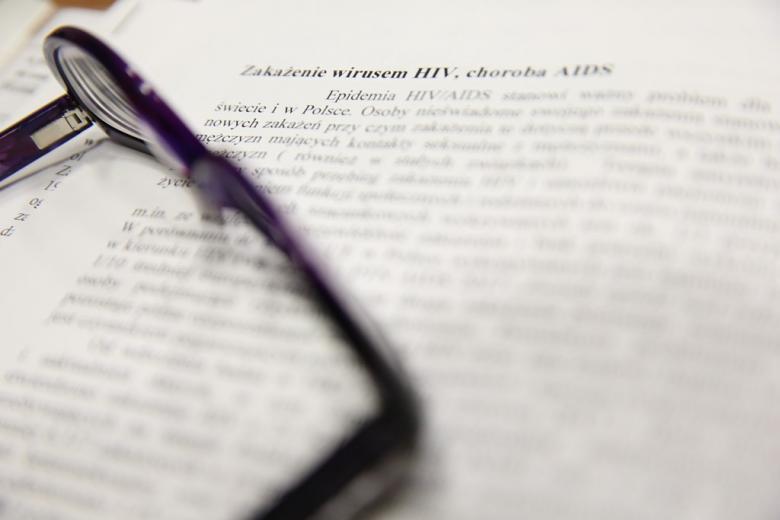 """Okulary i dokument. Widac tytuł Zakażenie wirsem HIV"""". Reszta nieczytelna"""