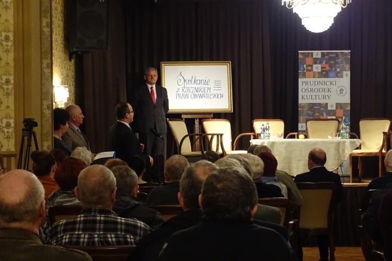"""Ludzie siedzą na zabytkowej sali, mężczyzna stoi, w głębi w eleganckiej oprawie napis """"Spotkanie z Rzecznikiem Praw Obywatelskich"""""""