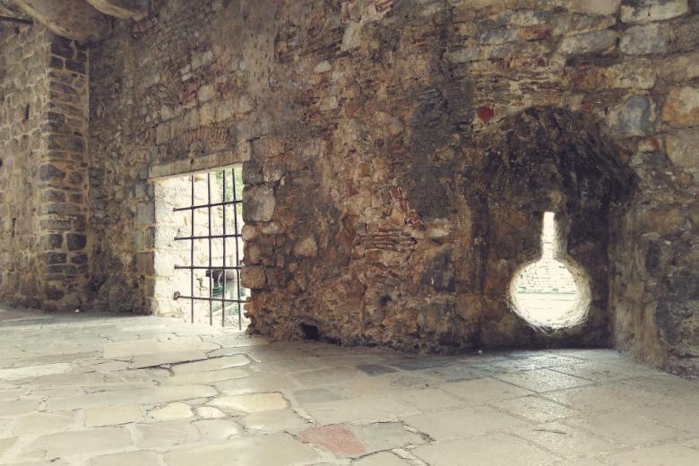 Zakratowane okno zamkowe a obok otwór pozwalający na wyjście