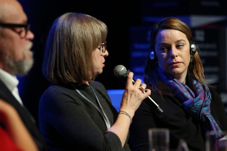 Panelista i panelistki rozmawiają, jedna ma słuchawki