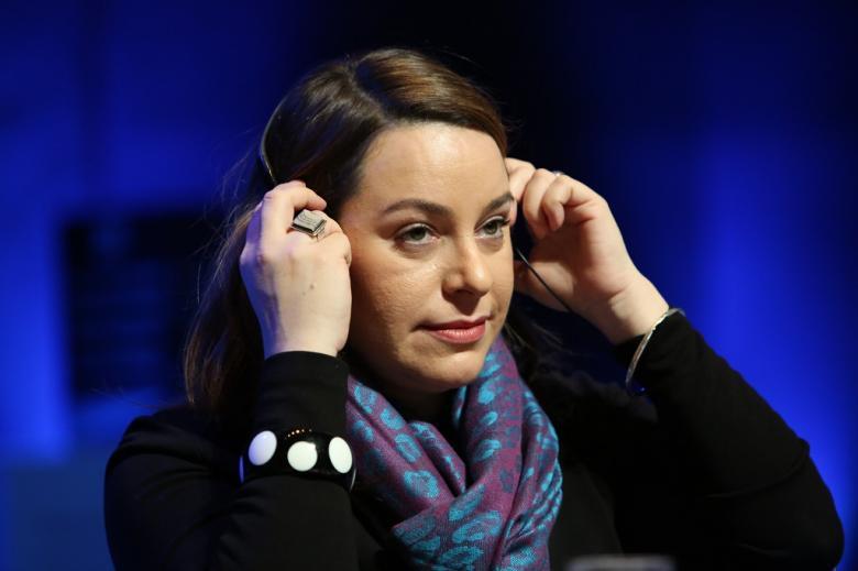 Kobieta zakłada słuchawki z tłumaczeniem debaty
