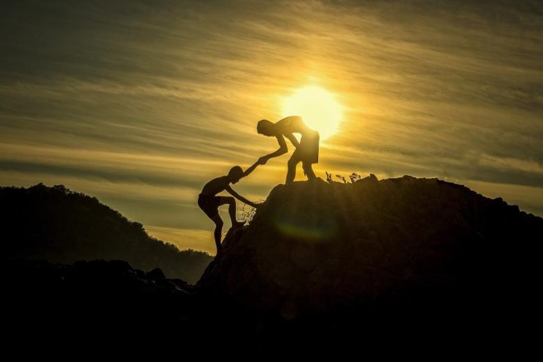 Ludzie pomagają sobie w czasie wspinaczki w górach