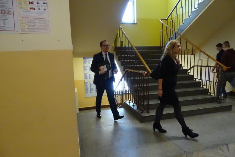 Mężczyzna i kobieta idą przez korystarz szkolny