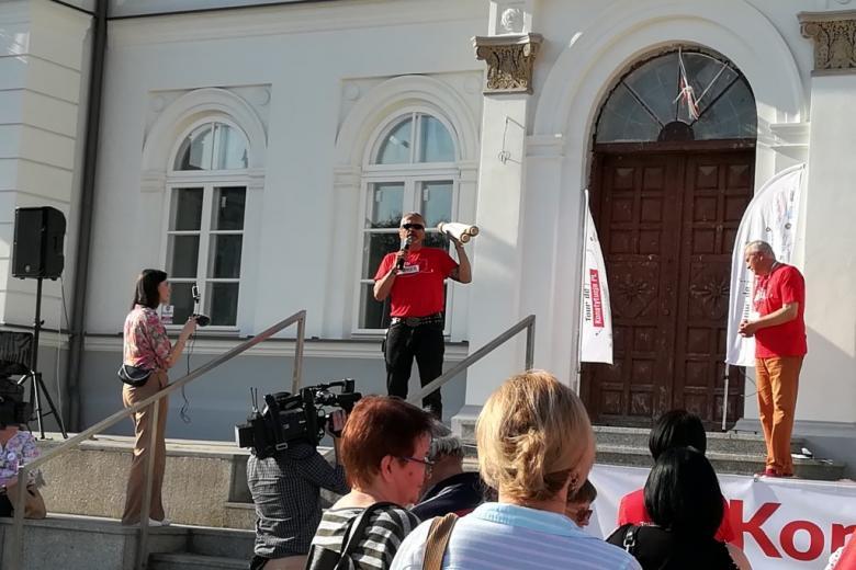 Mężczyzna w czerwonej koszulce trzyma zwój