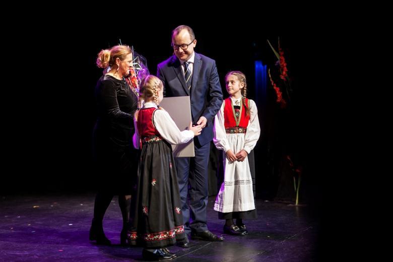 Dziewczynki w norweskich strojach wręczają dyplom męzczyźnie