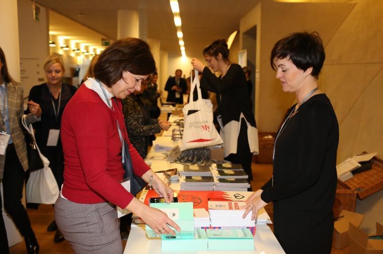 Ludzie przeglądają publikacje wyłożone na stolach
