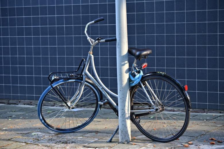 Rower przypięty do słupa, niebieska ściana