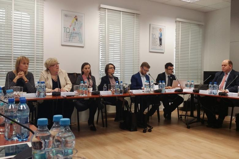zdjęcie: kilka osób siedzi przy brązowych stołach