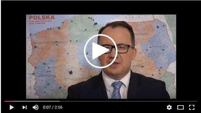 zdjęcie: mężczyzna w okularach stoi na tle mapy Polski
