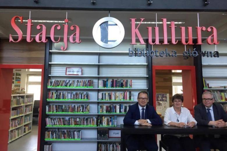 Trzy osoby w bibliotece