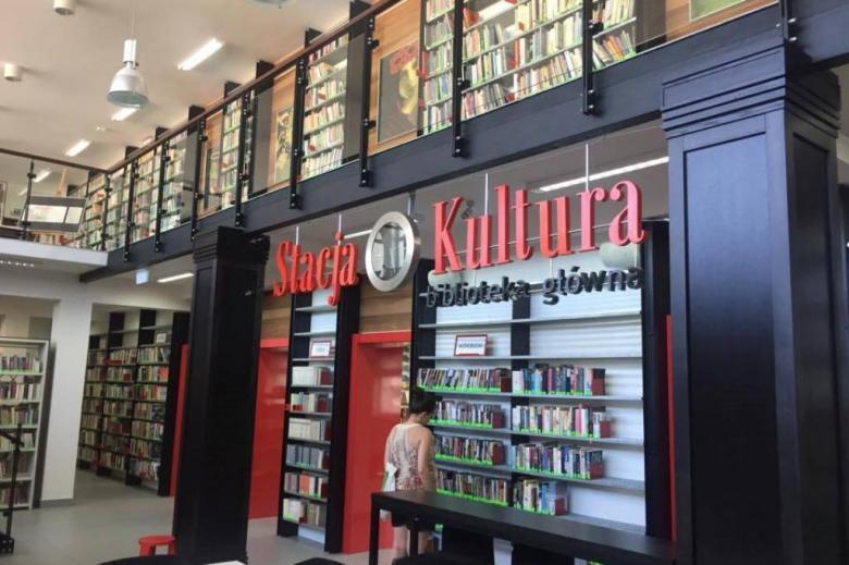 """Dwupoziomowe wnętrze z dużym napisem """"Stacja Kultura"""". Półki z książkami"""