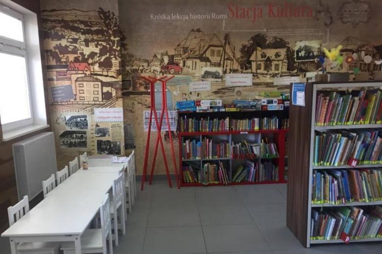 Półki z książkami o historii Rumii. Czerwony regał i ściana ozdobiona wielkim wizerunkiem starego miasta