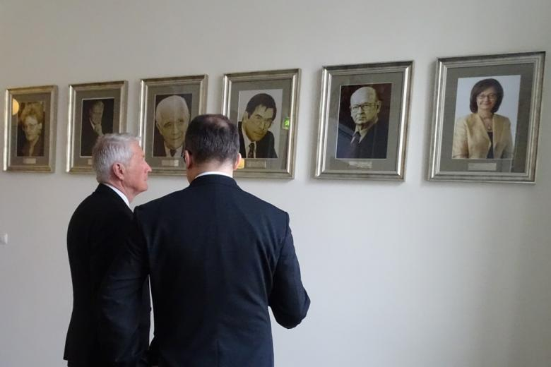 Zdjęcie: dwóch mężczyzn ogląda portrety na ścianie