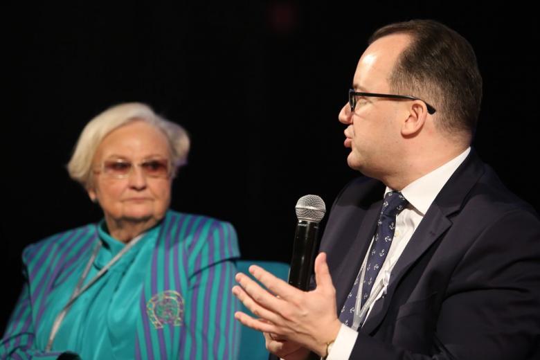 zdjęcie: na pierwszym planie mężczyzna mówi do mikrofonu, w tle widać kobietę