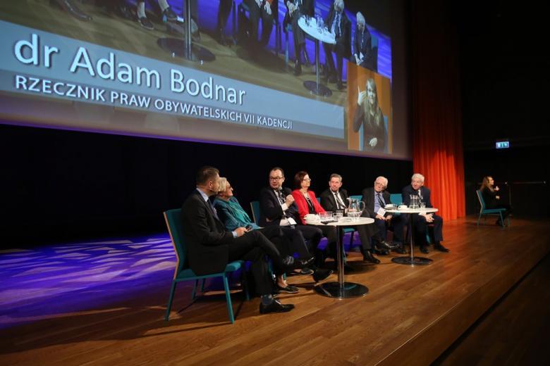 zdjęcie: na scenie siedzi kilka osób