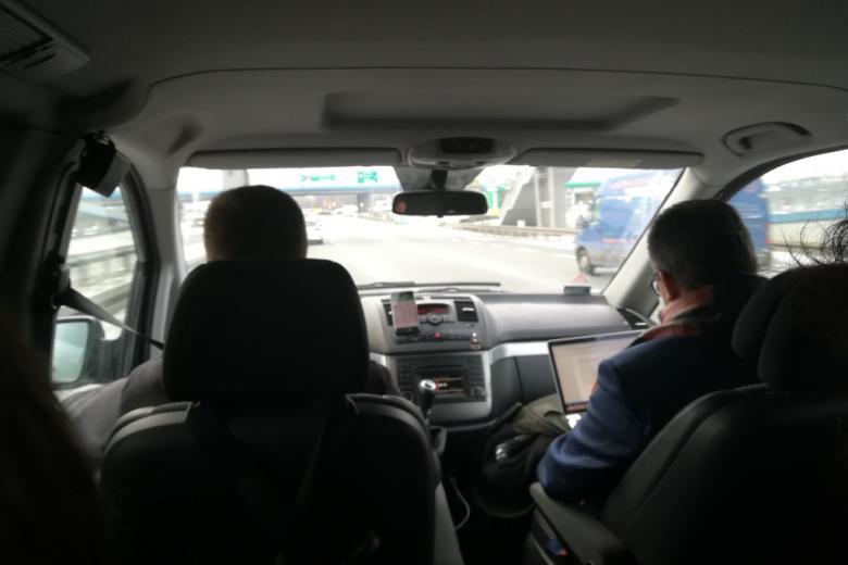 Wnętrze busa. Widać kierowcę i mężczyznę pracującego na komputerze na miejscu pasażera