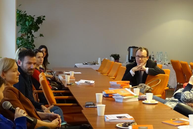 Adam Bodnar w geście słuchania przy stole, wokół ludzie