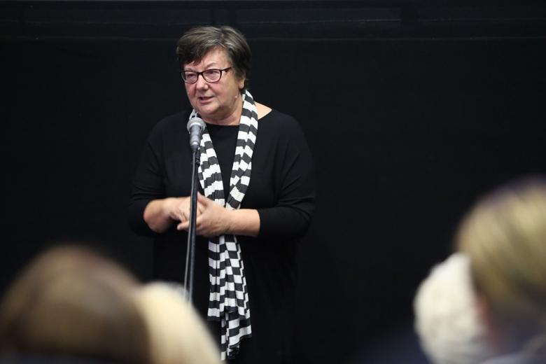 Kobieta w ciemnej sukni i biało-czarnym szalu