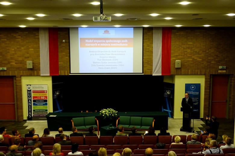 """Mężczyzna przy mówinicy w auli uniwersyteckiej. Na ścianie prezentacja """"Model wsparcia społecznego osób starszych w środowisku zamieszkania"""""""