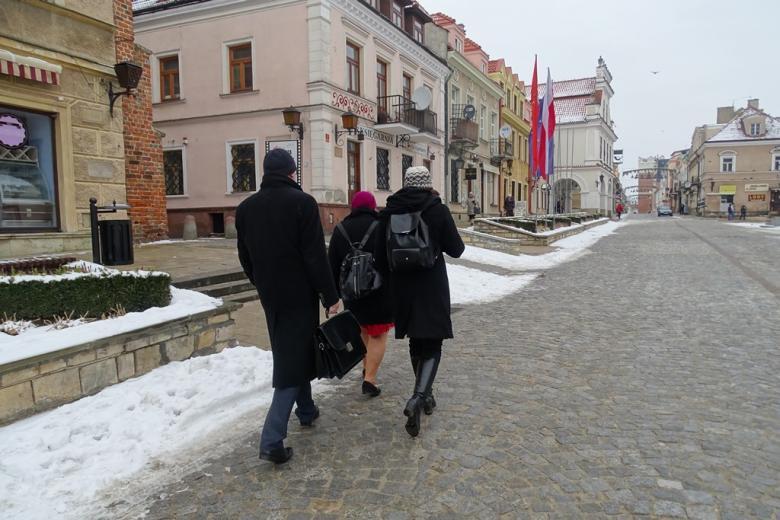 Troje ludzi idzie przez zabytkowe miasto