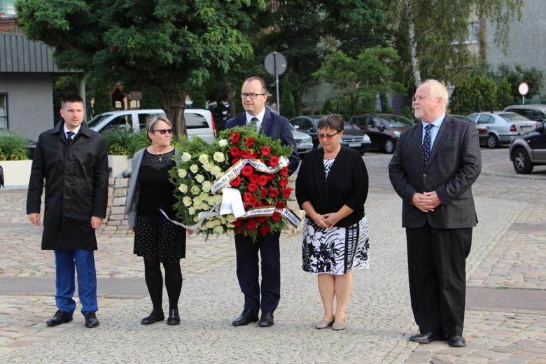 Pięć osób: dwie kobiety i trzech mężczyzn. Mężczyzna w środku trzyma wieniec z białych i czerwonych kwiatów