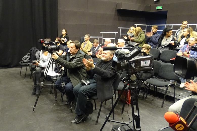 Ludzie na sali klaszczą, kamery