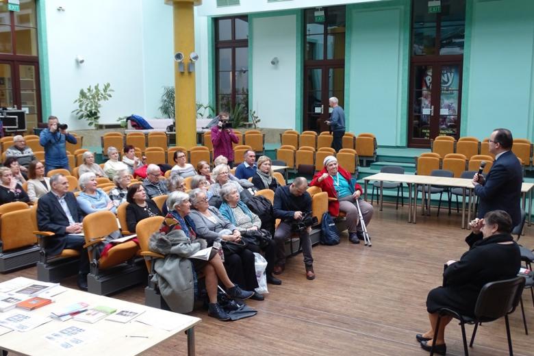 Ludzie siedzą na sali, pomarańczowe krzesła
