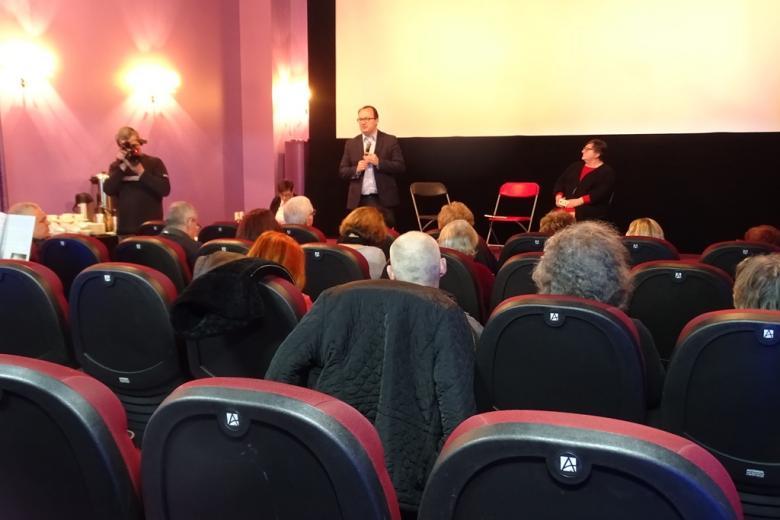 Ludz8ie na sali kinowej, mężczyzna stoi