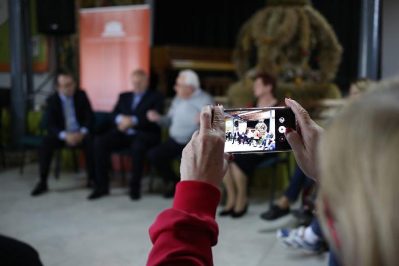 Ludzie siedzą w kręgu w zabytkowym wnętrzu, ktoś robi zdjęcie telefonem komórkowym