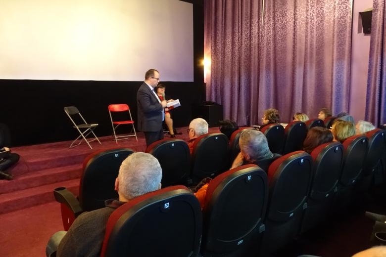 Mężczyzna z książką, ludzie na sali kinowej