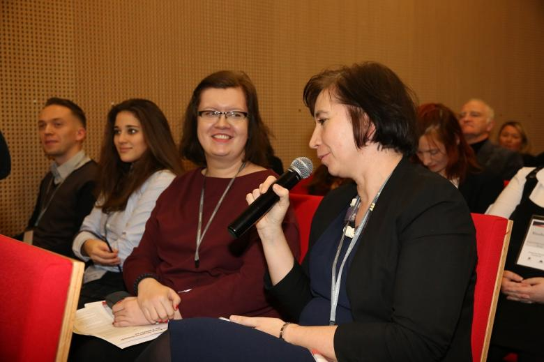 Sala konferencyjna, kobieta mówi do mikrofonu, czerwone krzesla