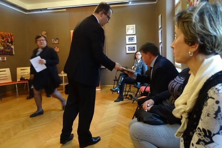 Zdjęcie: Adam Bodnar wręcza uczestnikowi spotkania materiały informacyjne