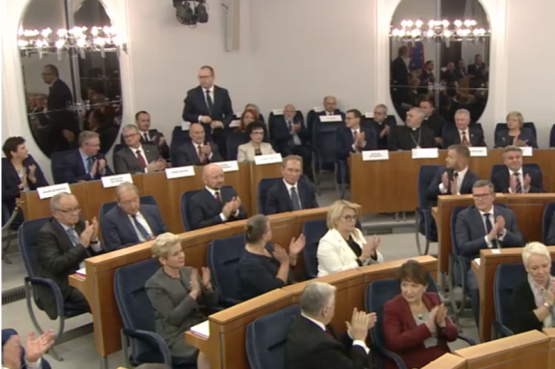 Screen z transmisji. Mężczyzna w głębi sali senatorskiej stoi i kłania się, reszta osób siedzi