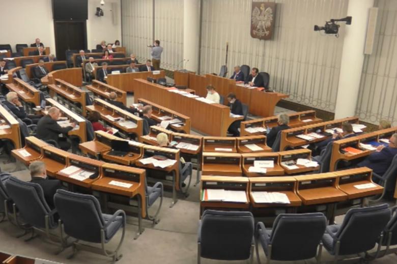 Ludzie na sali plenarnej, częściowo pustej
