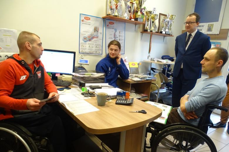Dwaj mężczyźni na wózkach, na ścianach puchary i medale