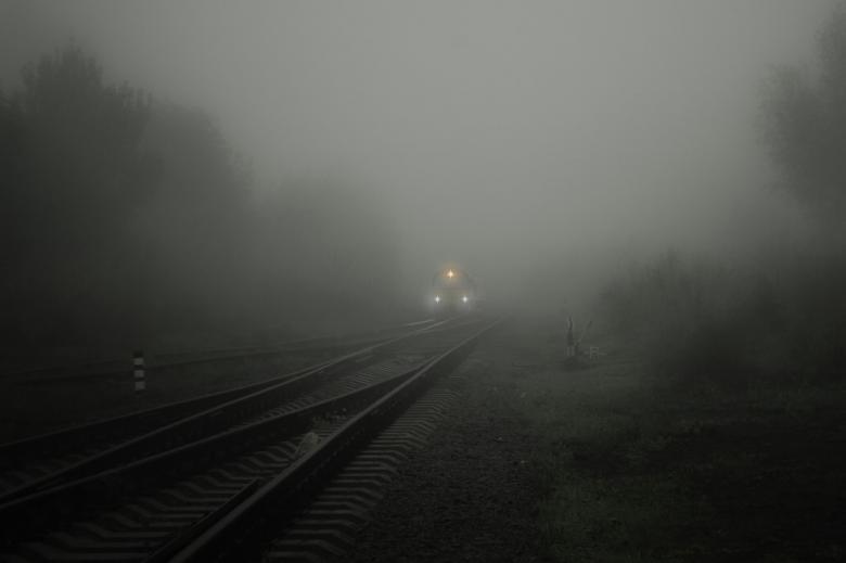 Rozjazd kolejowy. Lokomotywa wyłania się z ciemnej mgły