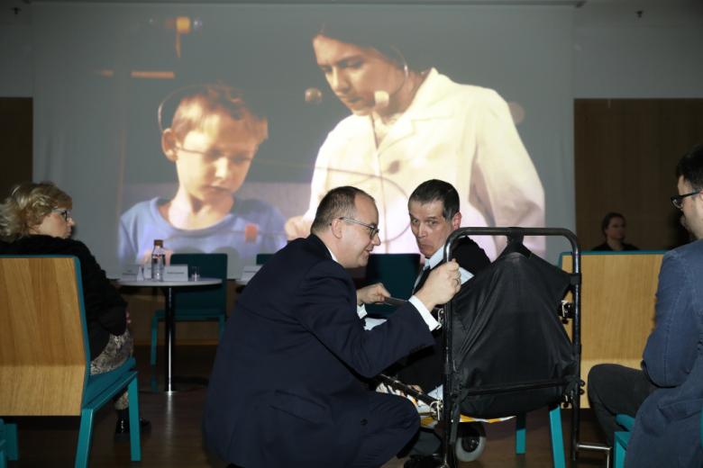 Rozmawiają dwaj mężczyźni, jeden na wózku, w tle - kadr z filmu