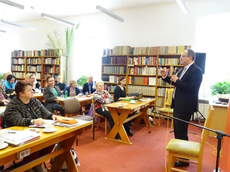 Zdjęcie: Adam Bodnar stoi przed zebranymi na sali. W tle półki z książkami