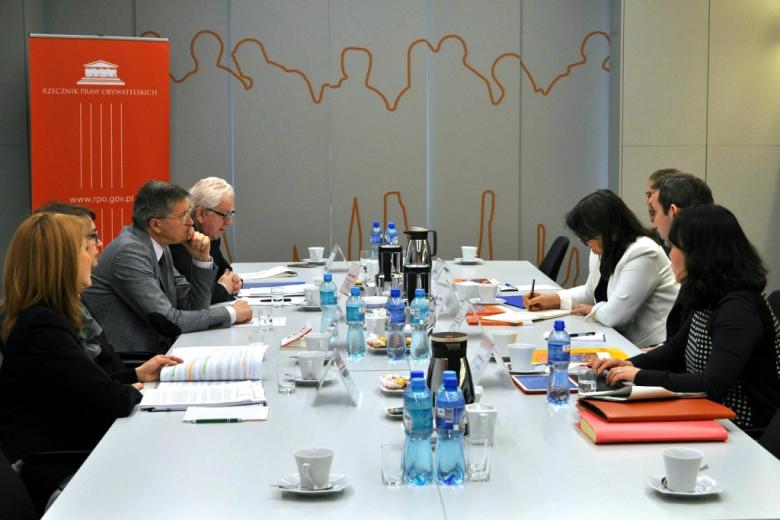 zdjęcie: sześć osób siedzi przy stole  i rozmawia, w tle widać pomarańczowy banner RPO