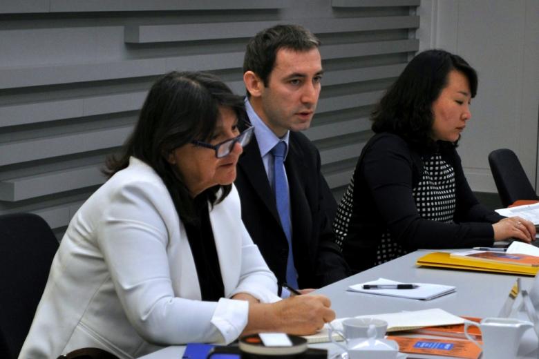 zdjęcie: dwie kobiet siedzą przy stole, pomiędzy nimi siedzi mężczyzna, kobieta na pierwszym planie jest w białym żakiecie
