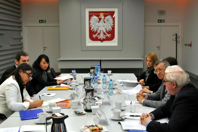 zdjęcie: po dwóch stronach stołu siedzi na przeciwko siebie sześć osób w tle na ścianie wisi godło Polski