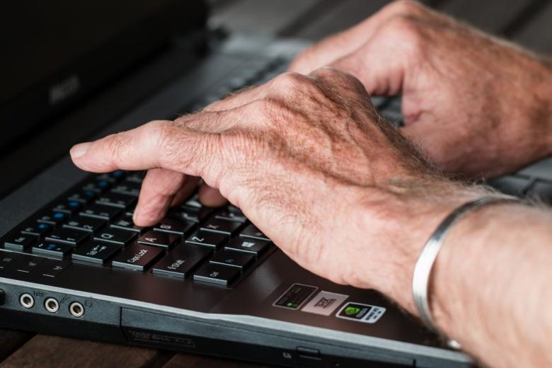 Ręce seniora na klawiaturze komputera